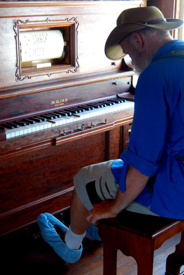 James operating the player piano that had entertained Admiral Peary on his trip to the North Pole